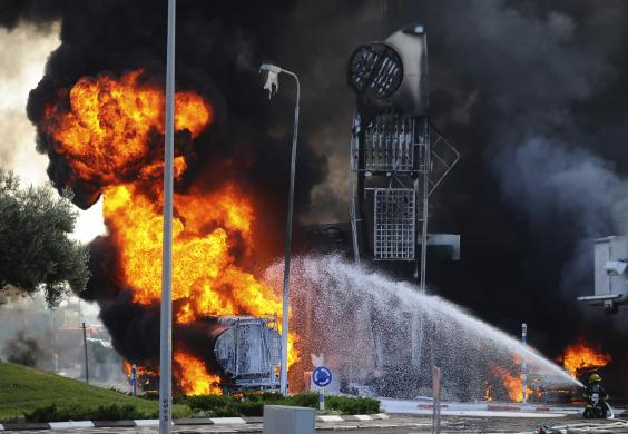 Israeli firefighters extinguish a fire that broke out after a rocket hit a petrol station in Ashdod