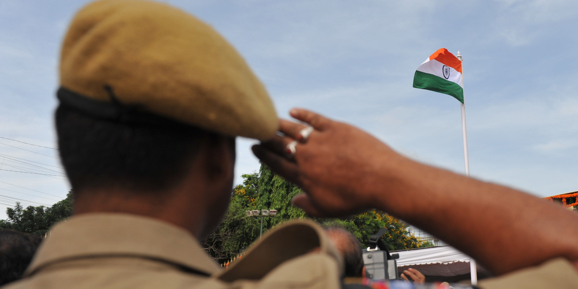 An Indian police salutes during the flag